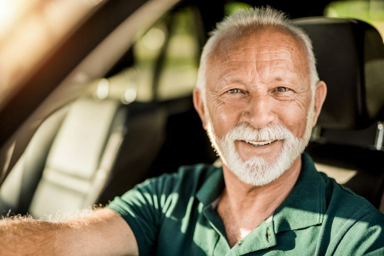 Headshot of happy senior man in his car looking at camera.