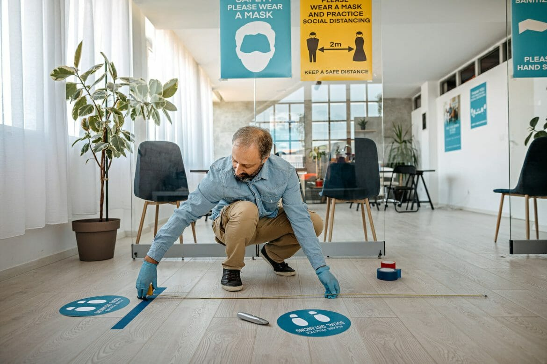 Man applying social distancing sign at office