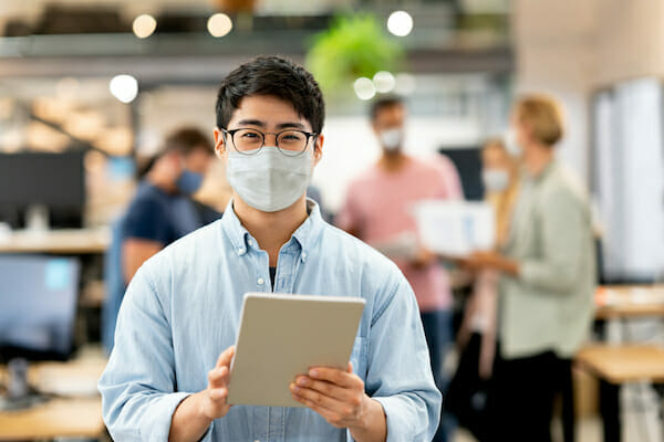 Asian man working online at a creative office and wearing a facemask