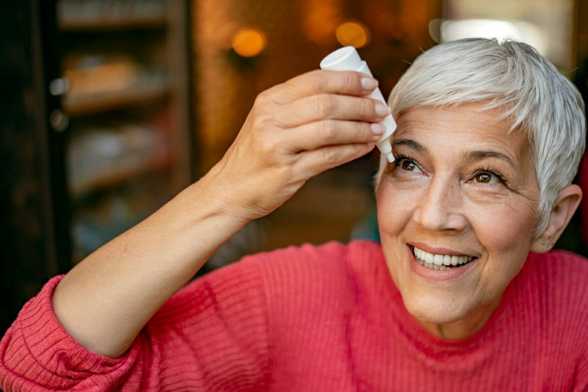 Photo of senior woman putting eye drop, closeup view of elderly person using bottle of eyedrops in her eyes. Sick old woman suffering from irritated eye, optical symptoms. Health concept. Concept of eye treatment, vision improvement, poor eyesight