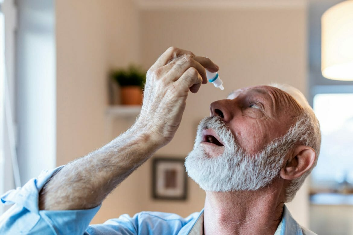 Man using eye drops for glaucoma