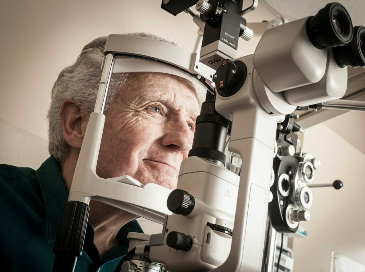 Ophthalmologist giving eye exam to senior patient