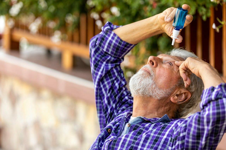 Senior Caucasian man inserting eye-drops