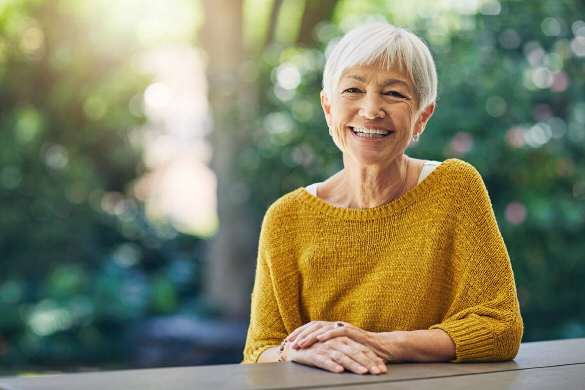 Shot of a happy senior woman sitting at a table in her backyard