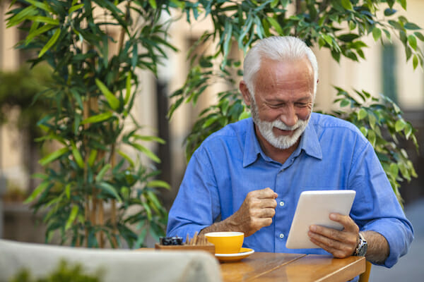 Senior man using a digital tablet. Leisure Lifestyle Relaxation Solitude Technology Concept. Senior man reading news on digital tablet. Successful senior businessman in cafe.